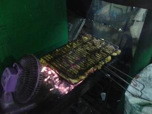 Ayam yang sedang dibakar di atas bara api.